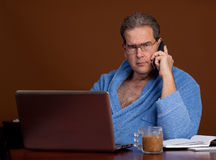 Unhappily working in a bathrobe Stock Photography