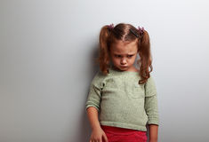 Unhappy abandoned kid girl looking down on blue background. With empty copy space Stock Photography