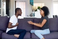 Unhappy African American couple quarreling, sitting on sofa at home stock images