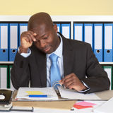 Unhappy african businessman at office. Looking at his paperwork at desk royalty free stock photo