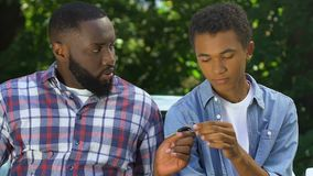 Unhappy afro-american father taking car keys from son looking guilty, punishment