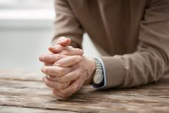Unhappy aged man being alone. Feeling of loneliness. Unhappy cheerless aged man holding his hands together while feeling lonely Stock Images