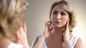 Unhappy aged woman looking in mirror at home, touching face, aging process royalty free stock image
