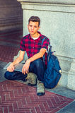 Unhappy American Student thinking outside in New York. Dressing in a short sleeve, black, red patterned shirt, jeans, boot shoes, carrying shoulder bag, holding Royalty Free Stock Images
