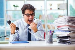 The unhappy angry call center worker frustrated with workload. Unhappy angry call center worker frustrated with workload Royalty Free Stock Photography