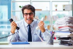The unhappy angry call center worker frustrated with workload. Unhappy angry call center worker frustrated with workload Royalty Free Stock Photo