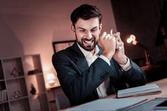 Unhappy angry man sitting and tearing the document. Wrong idea. Unhappy angry busy man sitting in the cabinet looking down and tearing the document Royalty Free Stock Photo
