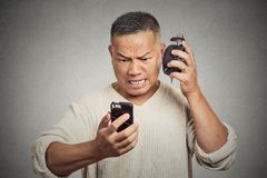 Unhappy angry middle aged man with alarm clock looking at smart phone Stock Images