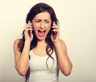 Unhappy angry stressed woman holding two mobile phones near the. Ears and crying with wide open mouth. Toned vintage portrait Stock Photos