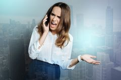 Unhappy angry woman being stressed out. Nervous breakdown. Unhappy angry young woman talking on the phone and shouting at her interlocutor while being stressed Royalty Free Stock Photography
