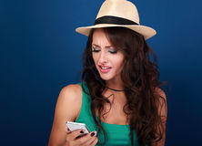 Unhappy angry woman in hat looking on mobile phone in stress emo. Tion on blue background Stock Images
