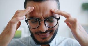 Unhappy Arabian man suffering from headache touching head massaging temples. Unhappy Arabian man is suffering from severe headache touching his head massaging stock video