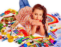 Unhappy artist woman lying on paint palette Stock Images