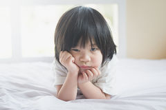 Unhappy asian baby lying on white bed Royalty Free Stock Photo