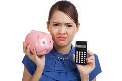 Unhappy Asian business woman with calculator and piggy bank Royalty Free Stock Photos
