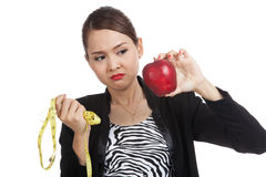 Unhappy Asian business woman diet with red apple and  measuring Royalty Free Stock Photos