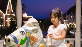 Unhappy Asian girl riding on a house merry go round. Royalty Free Stock Image