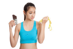 Unhappy Asian healthy girl with chocolate and measuring tape Royalty Free Stock Image