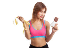 Unhappy Asian healthy girl with chocolate and measuring tape Royalty Free Stock Images