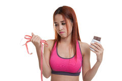 Unhappy Asian healthy girl with chocolate and measuring tape. Royalty Free Stock Photo