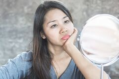 Unhappy Asian Woman Age 40 Checking Her Dark Eyes Circle Problem In Mirror Stock Photography