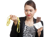 Unhappy Asian woman on diet with chocolate bar and measuring tap Stock Photos