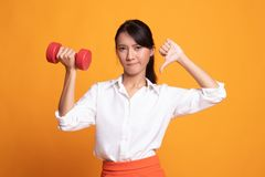 Unhappy Asian woman thumbs down with dumbbells. On yellow background royalty free stock photo