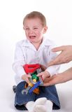 Unhappy baby. Hands trying to help a little boy crying stock photo