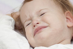 Unhappy baby in bed Stock Image