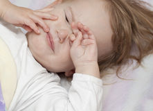 Unhappy baby in bed Stock Images