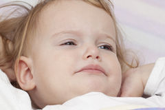 Unhappy baby in bed Stock Photo