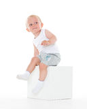 Unhappy baby boy sits on cube. Stock Photo