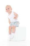 Unhappy baby boy sits on cube. Stock Photography