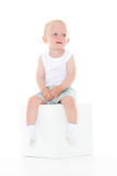 Unhappy baby boy sits on cube. Royalty Free Stock Photography