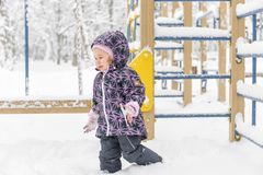Unhappy baby girl walks during snowfall royalty free stock images