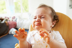 Unhappy Baby In High Chair At Meal Time Royalty Free Stock Photography