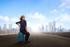 Unhappy beautiful asian traveler woman with luggage waiting tran Royalty Free Stock Photo