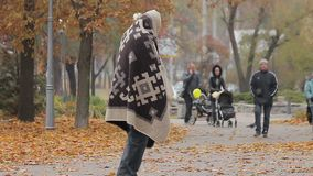 Unhappy beggar limping in autumn park, social vulnerability and poverty problem. Stock footage stock video