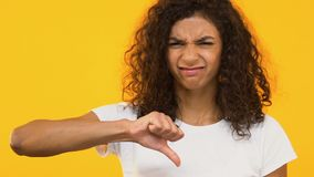 Unhappy biracial girl showing thumb down, dissatisfied with service, dislike. Stock footage stock footage