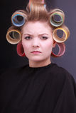 Unhappy blond girl hair curlers rollers. salon. Royalty Free Stock Photos