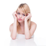 Unhappy Blond Woman with Head in Hands. Young Blond Woman with Head in Hands Looking Miserable in White Studio stock photo
