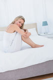 Unhappy blonde getting a stomach pain in bed Royalty Free Stock Images