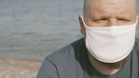 Unhappy bold man close up portrait wearing medical face mask in public beach places. Unhappy with coronavirus effect on