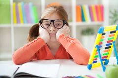 Unhappy bored red-haired girl doing her homework at home Royalty Free Stock Images