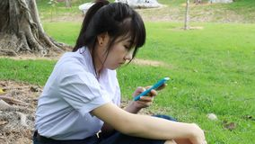 Unhappy Bored thai student teen Using Smartphone. Sitting On Park stock video footage