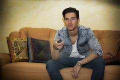Unhappy, bored, unsure young man with remote control watching TV Stock Images