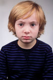 Unhappy Boy. A frowning stressed little 6 year old blond boy with an expression of dread or fear on his face Royalty Free Stock Image