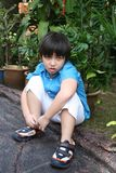 Unhappy boy. In blue shirt sitting in the park Royalty Free Stock Images