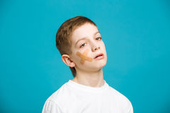 Unhappy boy with adhesive plaster on his cheek Royalty Free Stock Images