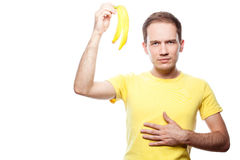 Unhappy boy with banana skin. Disappointed and hungry handsome guy holding banana skin over white background royalty free stock images